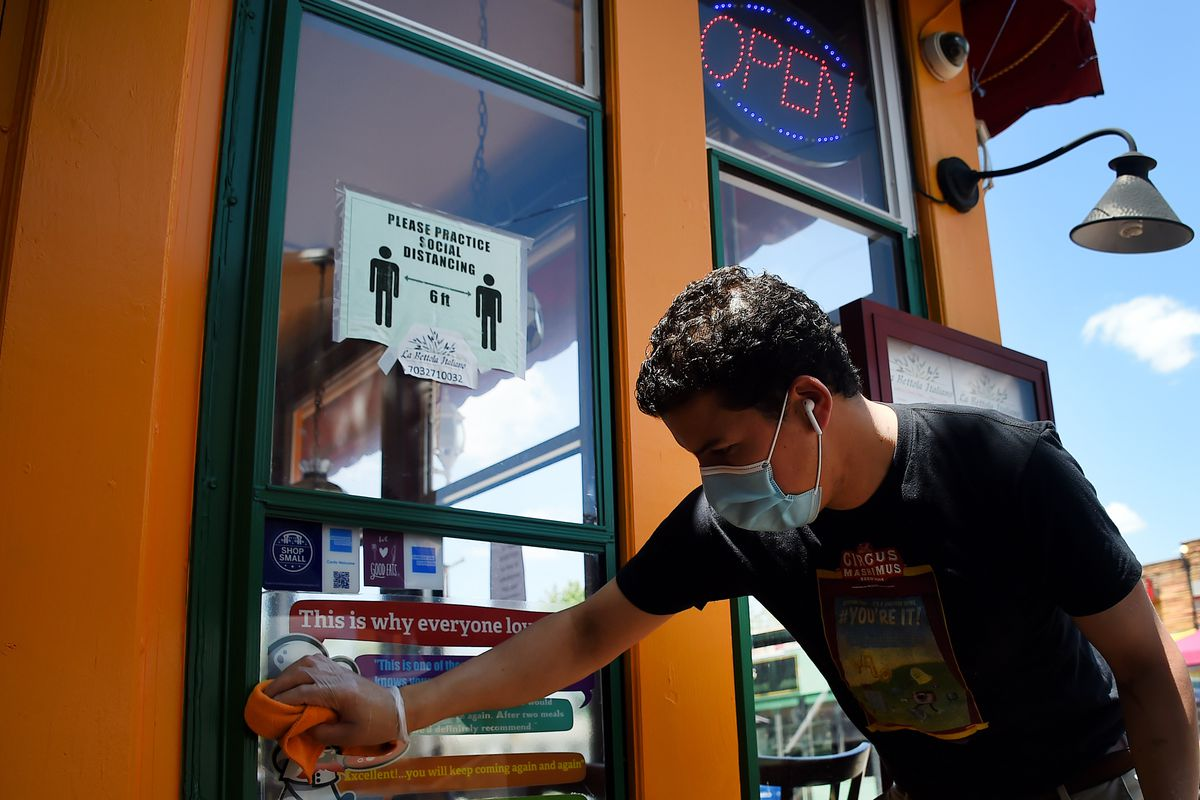 A man wearing gloves and a face mask wipes down the surface of a window with a rag.