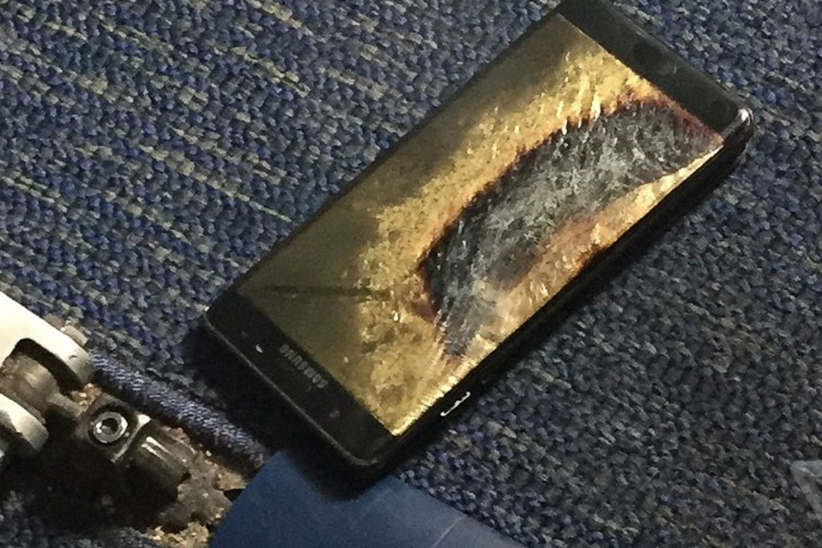 A Samsung Galaxy Note 7 lying on the floor of a plane, industrial carpet in the back ground, with the screen cracked and scorched.