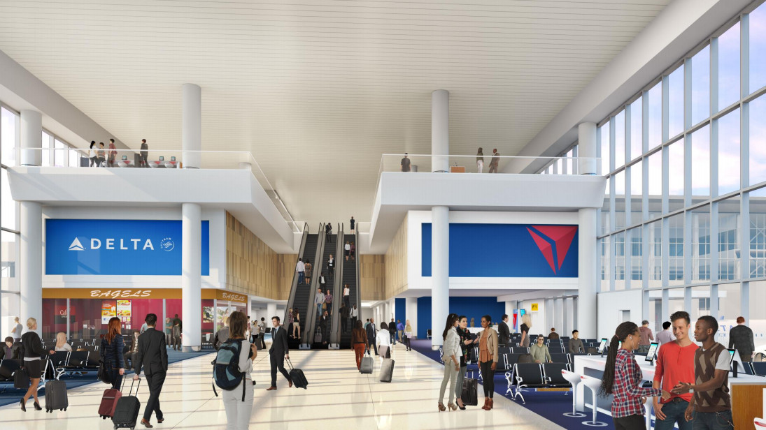 An airport terminal. There are floor to ceiling windows, shops, and seats for passengers. There are many people standing, sitting, and walking.