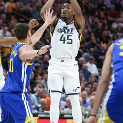 Utah Jazz guard Donovan Mitchell (45) puts up a shot over Golden State Warriors guard Klay Thompson (11) during the game at Vivint Arena in Salt Lake City on Tuesday, April 10, 2018.