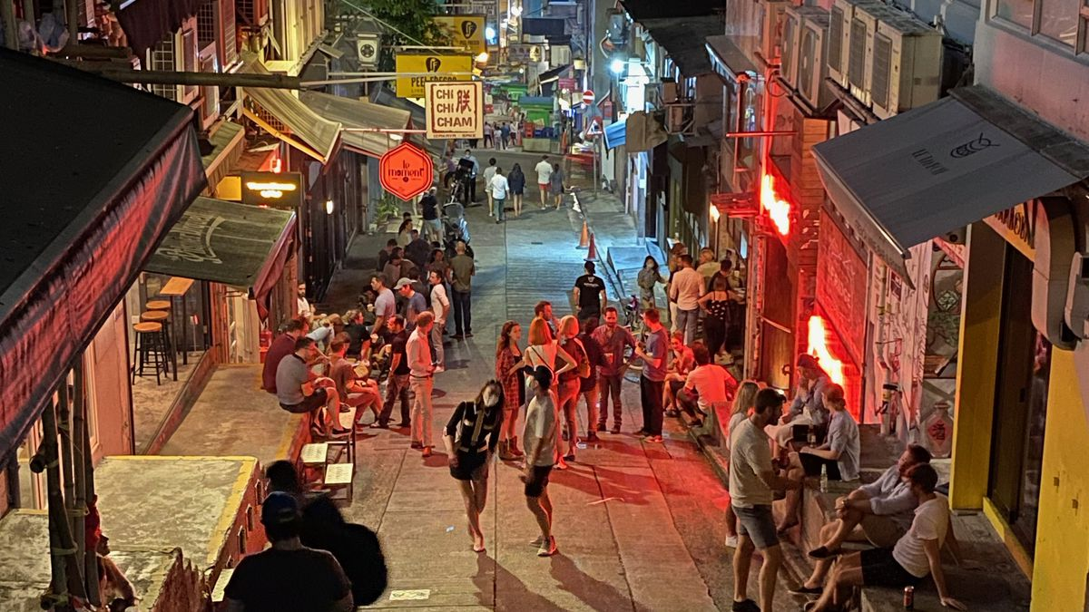 An overhead shot of a street half-full of club and restaurant goers, many wearing masks at night.