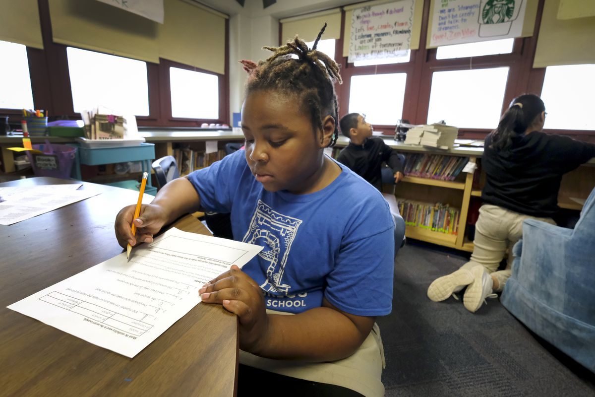 A student with a pencil works at a desk in a classroom at Thomas Gregg Neighborhood School, an elementary school in Indianapolis, Indiana.