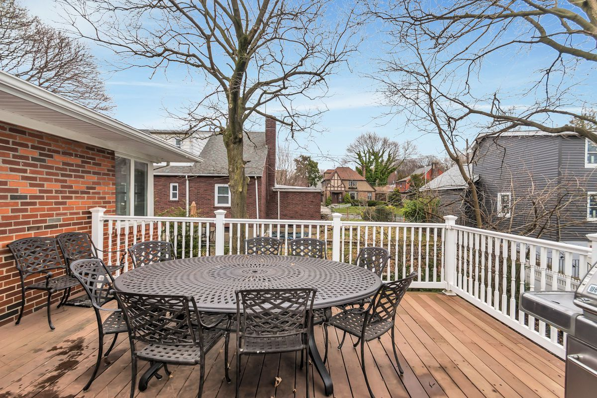 A wood deck with a round table, several chairs, and a barbecue grill.