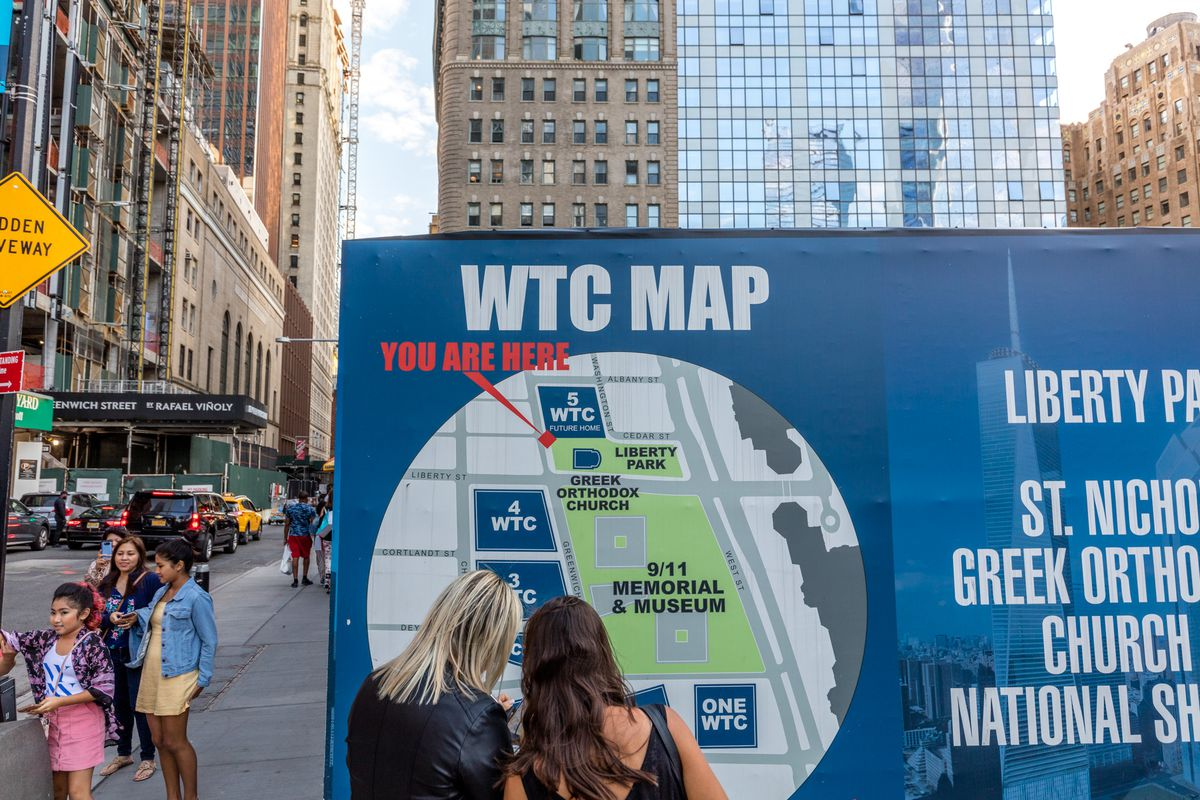 """Two women stand in front of a map showing buildings on a large urban campus. The text on the map reads """"WTC MAP."""""""
