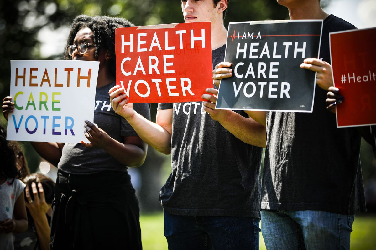 Demonstrators hold signs as Democratic leaders held a rally calling on the Trump administration to change its policy regarding the pre-existing conditions provisions of the Affordable Care Act, on June 26, 2018.