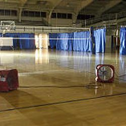 Fans blow on the hardwood volleyball court on the main floor Monday. Water seeped into the space between the raised court and the floor.