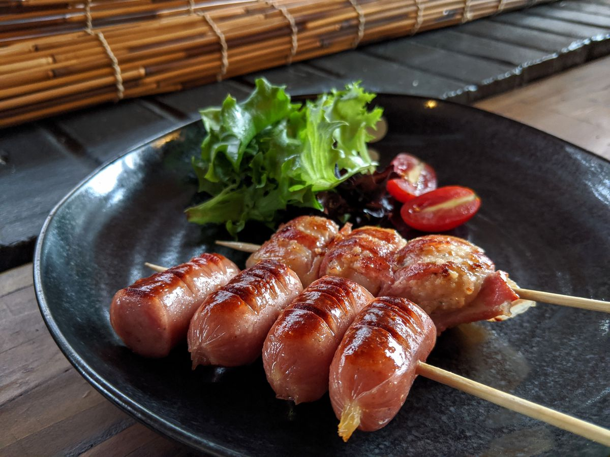 Two wooden skewers of meat on a blue plate —one with pieces of Japanese sausage and one with bacon-wrapped scallops- with a side of greens and sliced cherry tomatoes.