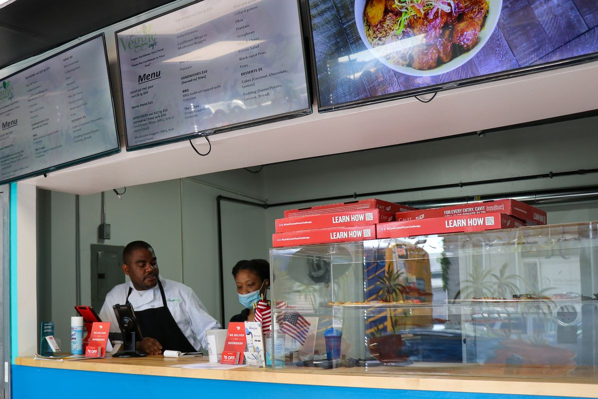 The chef Hulando Shaw stands behind a counter at Real Veggie Cafe