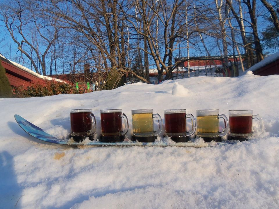 a shotski with six beers sits in a snowy embankment