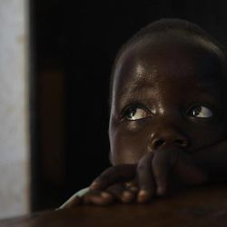 """In this photo taken Friday, April 27, 2012, daughter Betty, 3, looks up at her mother Adye Sunday, 25, unseen, who was abducted when she was 13 by Lord's Resistance Army (LRA) leader Joseph Kony and forced to be one of his dozens of """"wives"""" and says he's also the father of her two children, at a center set up to help those who have left or fled the LRA, in Gulu, Uganda. Adye Sunday isn't sure about the calls to kill or capture LRA leader Joseph Kony, who inspires conflicted thoughts among some people in northern Uganda, despite more than 3,000 children being abducted by the LRA since 2008, according to the U.N. and Human Rights Watch."""