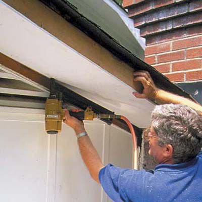 Man Attaches Replacement Soffit