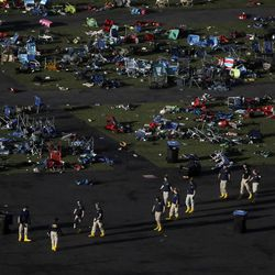 FILE - In this Oct. 3, 2017 photo, investigators work at a festival grounds across the street from the Mandalay Bay Resort and Casino where gunman Stephen Paddock unleashed more than 1,000 bullets on an outdoor concert, in Las Vegas. The fight is just beginning for many of the dozens of people still hospitalized in Las Vegas from the worst mass shooting in modern U.S. history. Ahead is pain, grueling rehabilitation and the prospect that they may never return to their normal lives. (AP Photo/Marcio Jose Sanchez, File)