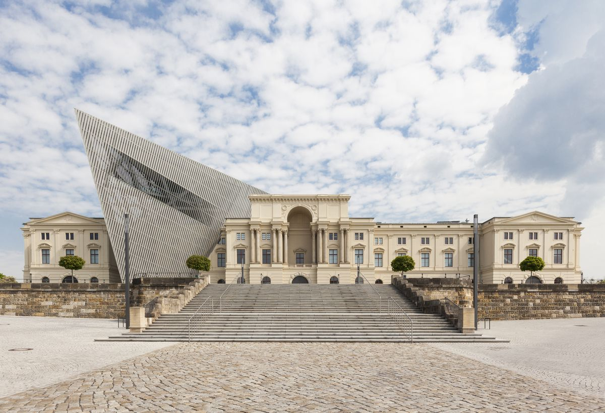 The exterior of the Bundeswehr Museum of Miltary History in Germany. The building is tan with columns flanking the entrance. There is a wedge shaped steel and glass structure to the side of the entrance.