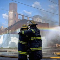 Firefighters greet each other in the aftermath of a fire in a warehouse on York Street near Kensington Avenue in Philadelphia on Monday, April 9, 2012. Two firefighters died after a wall collapsed on them while they fought the massive early-morning blaze.