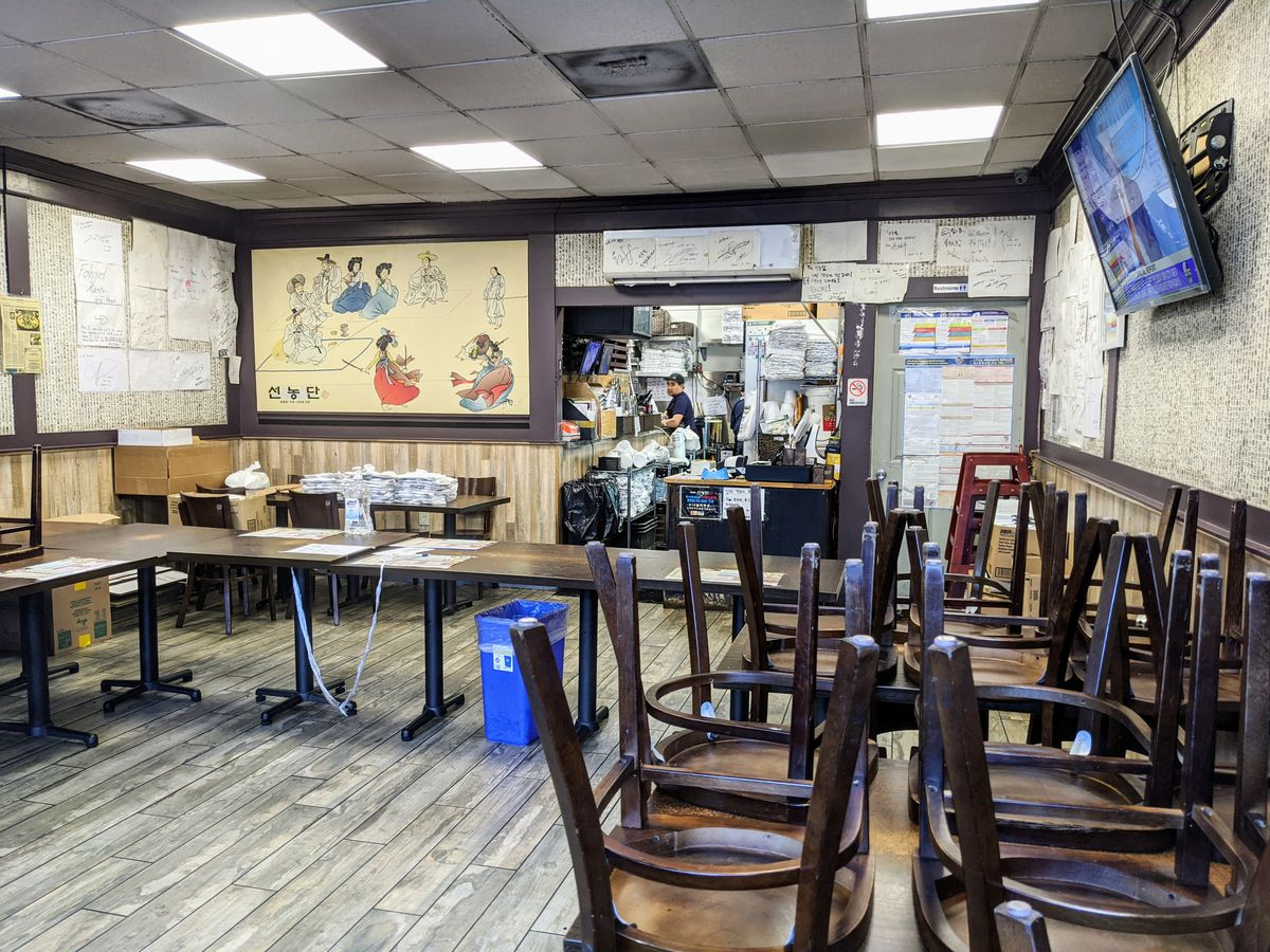 Inside Sun Nong Dan restaurant in Koreatown, where tables and chairs are stacked in the closed dining room. The kitchen is currently only serving takeout.