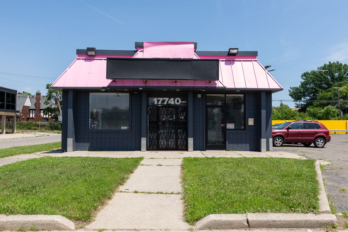 The building is shown on a sunny day. It has a black painted exterior and a hot pink roof with an unlabeled sign and a parking lot.