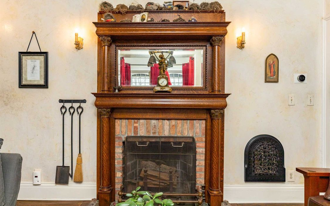 A fireplace has a brick interior and is lined with hand carved wood detail.