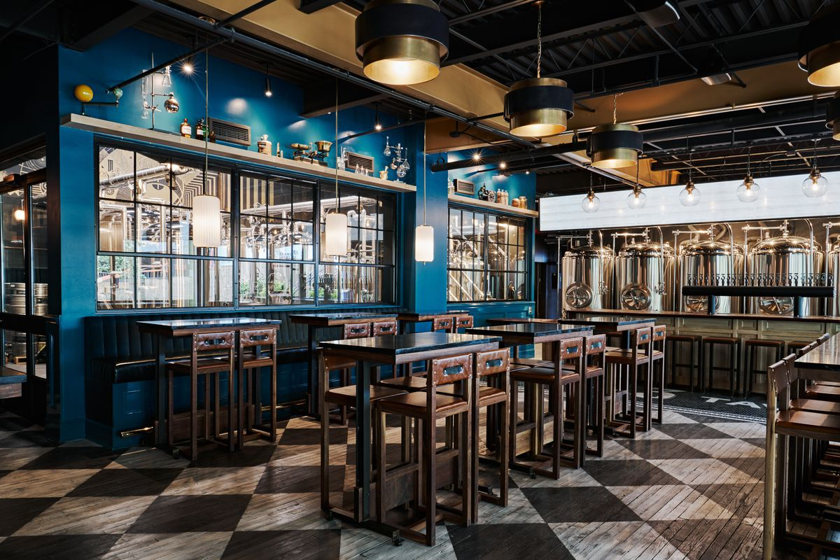 The downstairs bar at Three Taverns Imaginarium with six hightop tables and wooden chairs and blue wall with large window overlooking the brewing room behind a blue wall with paned windows