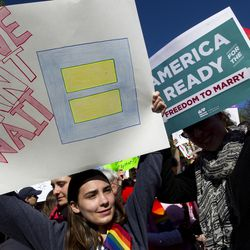 Demonstrators hold posters in front of the Supreme Court in Washington, Tuesday, April 28, 2015. The Supreme Court heard historic arguments in cases that could make same-sex marriage the law of the land.