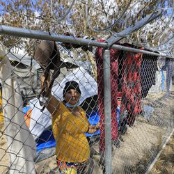 A Honduran migrant hangs clothes to dry on the fence surrounding the migrant camp in Matamoros, Tamaulipas, Mexico, on Tuesday, Feb. 23, 2021.
