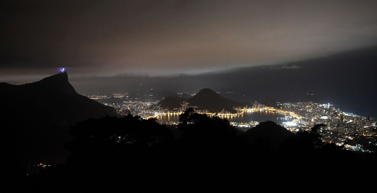 A picture taken at night shows Christ the Redeemer statue on Corcovado mountain and the lights of the city of Rio de Janeiro on August 3, 2016. | ERIC FEFERBERG/AFP/Getty