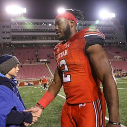 Utah running back Zack Moss greets a young fan as he leaves the field after his team's win over the Colorado Buffaloes at Rice-Eccles Stadium in Salt Lake City on Sunday, Nov. 26, 2017.