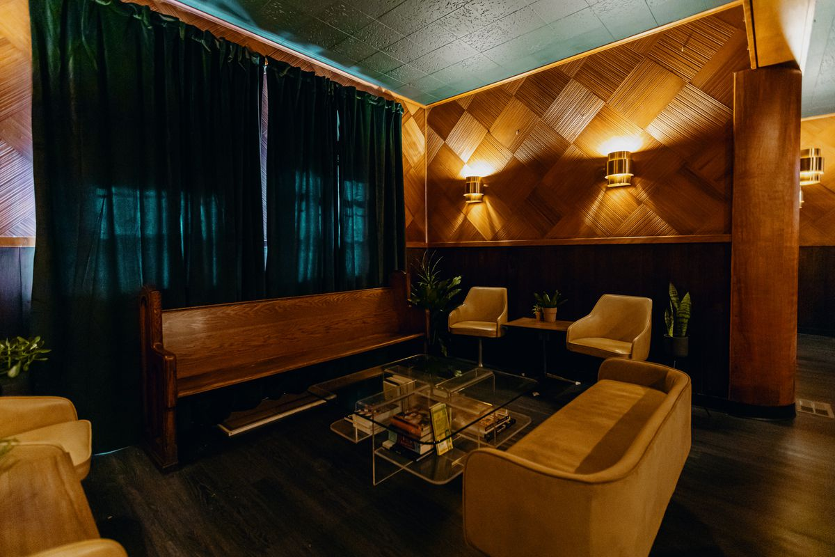 Green curtains block out sun from the windows in a seating area that features a wooden pew and mid-century chairs and sofas. The room features floor to ceiling wood paneling with squares of wood in a diamond pattern. The sconces are stylish brass deco.