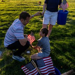 Tyler Hillstead, left, and his son Michael, 7, and daughter Ashley, 17, place flags at Larkin Sunset Gardens Cemetery in Sandy on Thursday, May 27, 2021. More than 200 youth volunteers from around the Salt Lake Valley honored military veterans for Memorial Day by placing 3,000 American flags on the graves of service members. In addition, they swept and polished headstones and helped beautify cemetery grounds.