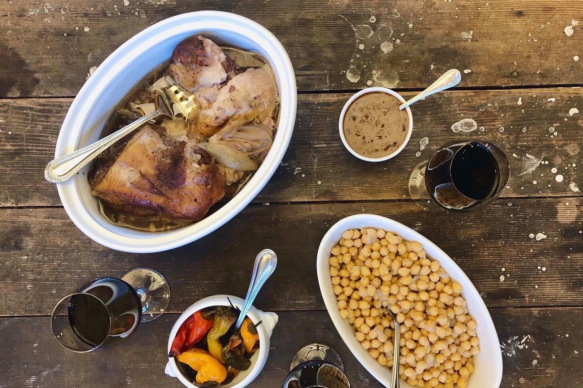 A collection of dishes from Boat Street Kitchen, including a pot of roasted chicken, with three glasses of red wine on a rustic wood table