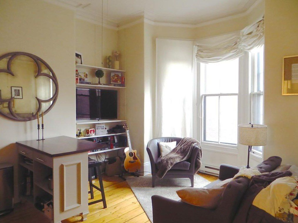 A sitting area in a studio with a bay window.