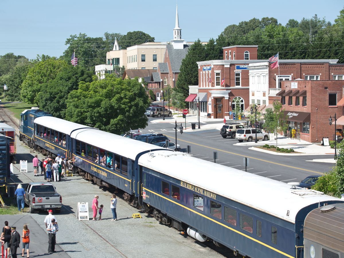 A blue train on a train track. There are people standing and walking next to the train. In the distance is a train station building with a red brick facade.