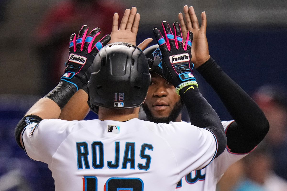 Miguel Rojas #19 of the Miami Marlins celebrates at home plate with Bryan De La Cruz #77 after hitting a two run homerun in the second inning against the Washington Nationals at loanDepot park
