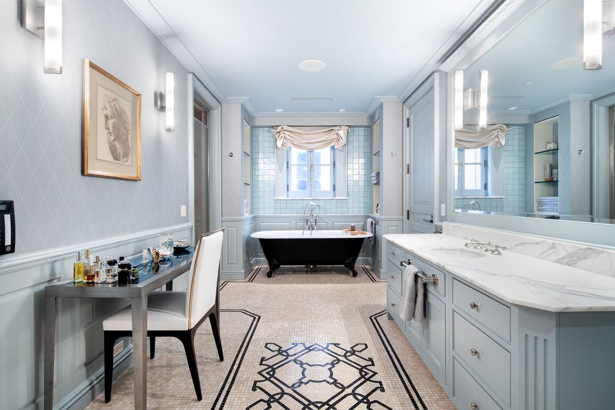 A long bathroom with a blue vanity with marble top, a freestanding clawfoot tub, and mosaic flooring.