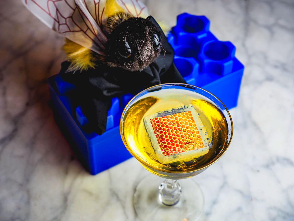 A cocktail in a martini glass with a giant toy bee on a blue Lego block.