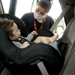 Kylie Kofford checks on her 9-month old son, Kohen Smith, after he was fitted into a new car seat during a drive-thru checkpoint at Shriners Hospitals for Children - Salt Lake City on Friday, Sept. 25, 2020. The checkpoint was an extension of the hospital's ongoing special needs car seat clinic, and a way to give back to the community.