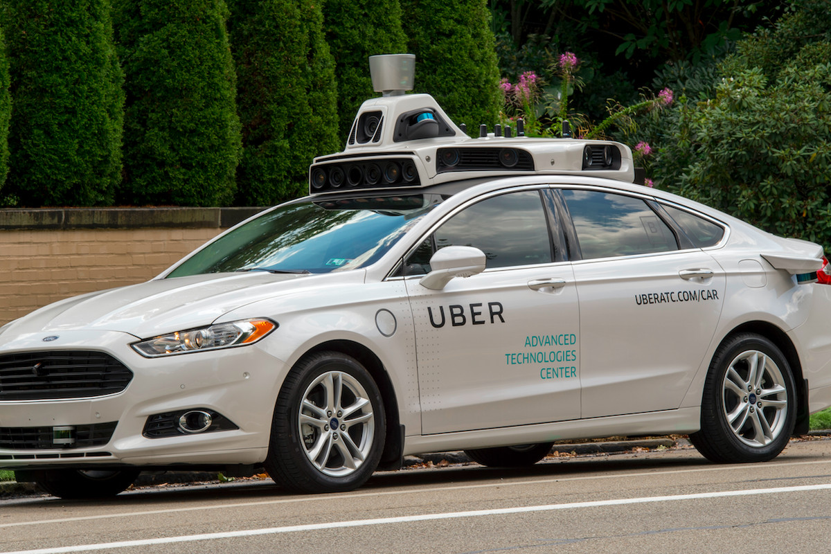 An Uber self-driving model car is shown parked by a tree-lined sidewalk.