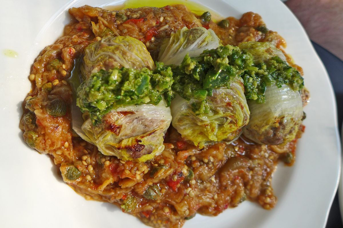 Three rolls of cabbage stand atop a slurry of tomato and eggplant.