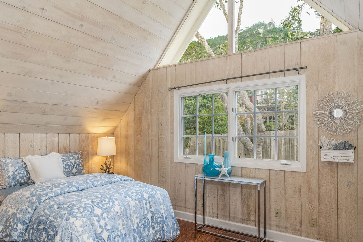 A guest bedroom features light birch walls, a blue and white comforter, and a large triangle window.