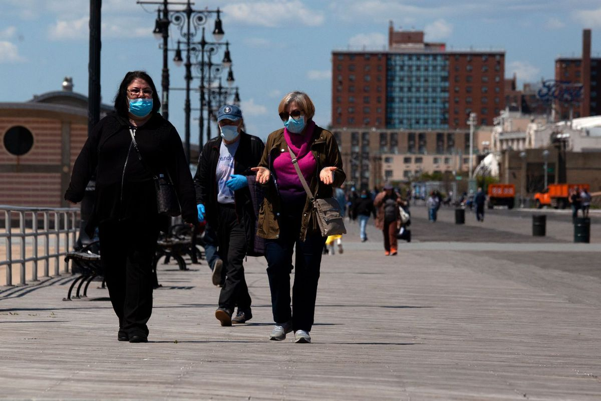 People enjoy a warm spring day on the Coney Island boardwalk during the coronavirus outbreak.
