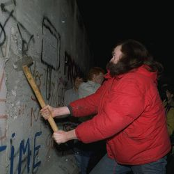 An unidentified Berliner tries in vain to demolish a segment of the Berlin Wall with a sledgehammer, November 11, 1989, at Bernauer Strasse, where East German police pulled down segments of the wall for a new passage.
