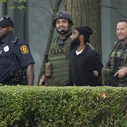 Pittsburgh police and SWAT members escort a suspect, center right, from a hostage-taking on the 16th floor at Three Gateway Center to a police van on  Friday, Sept. 21, 2012, in Pittsburgh. Klein Michael Thaxton, 22, surrendered just before 2 p.m., and the man he took hostage was unhurt, Police Chief Nathan Harper said.