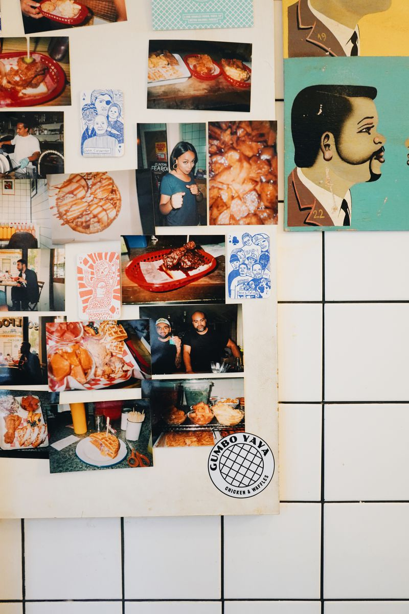 A close up of a colorful collection of photographs and drawings of people and food, all tacked up on a white tile wall inside Gumbo Yaya.