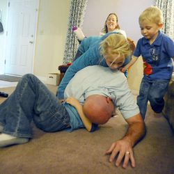 While Kelly Burton flips 6-year-old Porter, bottom, 8-year-old Mykenzie and 3-year-old Logan jump on his back and mom Mary looks on at the family's home Sept. 25.