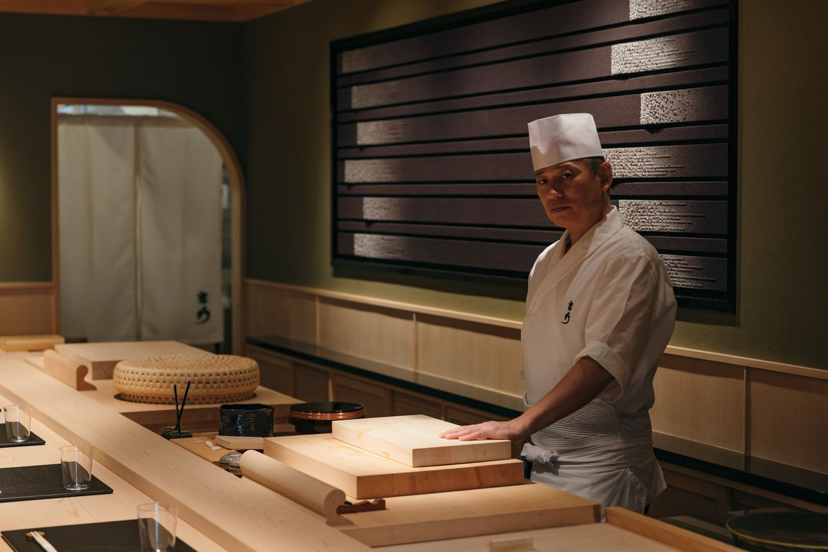 A chef in a white coat and hat stands behind a wooden sushi bar.