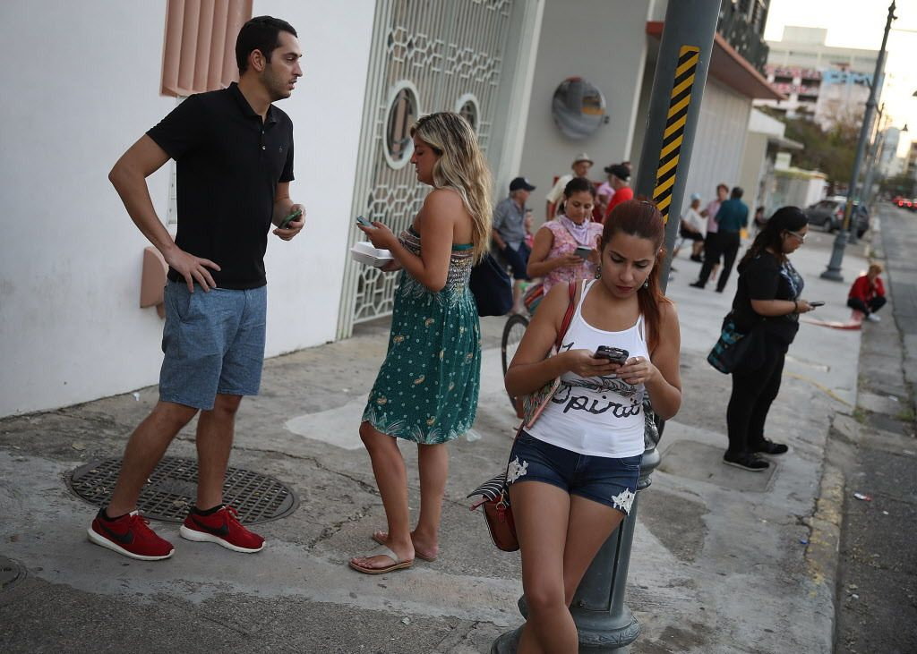 People take advantage of the Optico Fiber companies free Wi-Fi zone setup for those that don't have cell service to connect with friends or loved ones as they wait for the damaged telephone grid to be fixed after Hurricane Maria passed through the area on