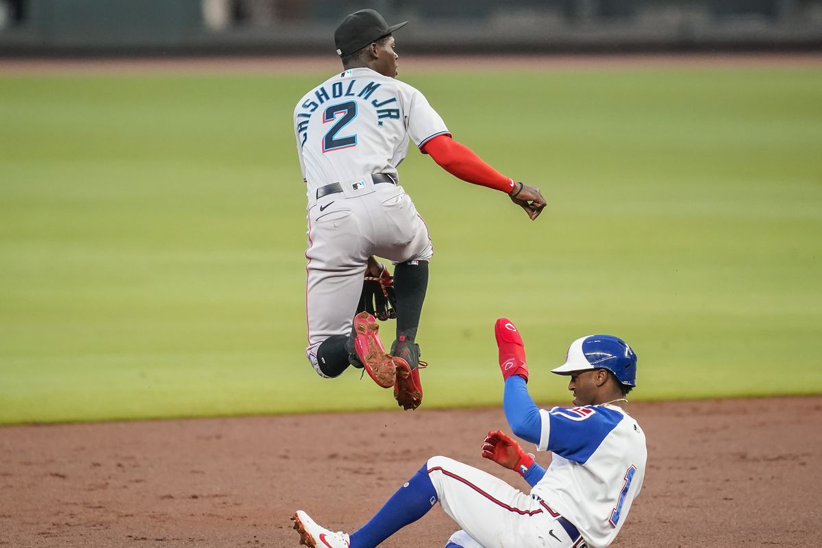 Miami Marlins second baseman Jazz Chisholm Jr. (2) jumps over Atlanta Braves second baseman Ozzie Albies (1) as he throws to first base to complete a double play during the second inning at Truist Park.