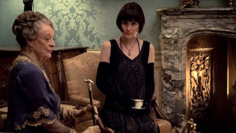 """Maggie Smith and Michelle Dockery sit by the fireplace and drink tea in the """"Downton Abbey"""" movie."""