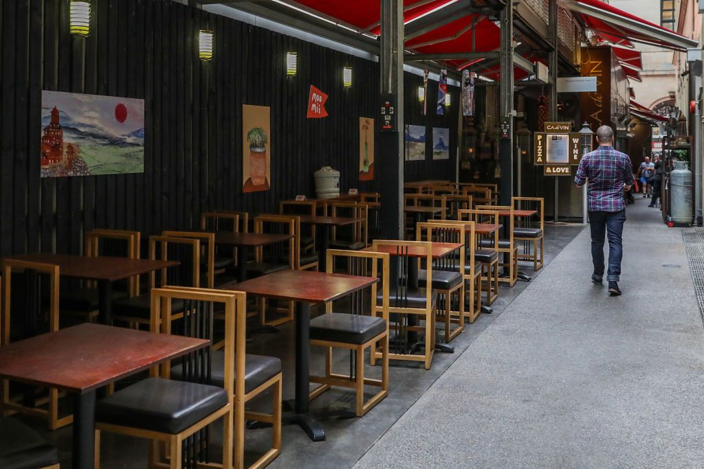 A server walks by rows of empty tables and chairs