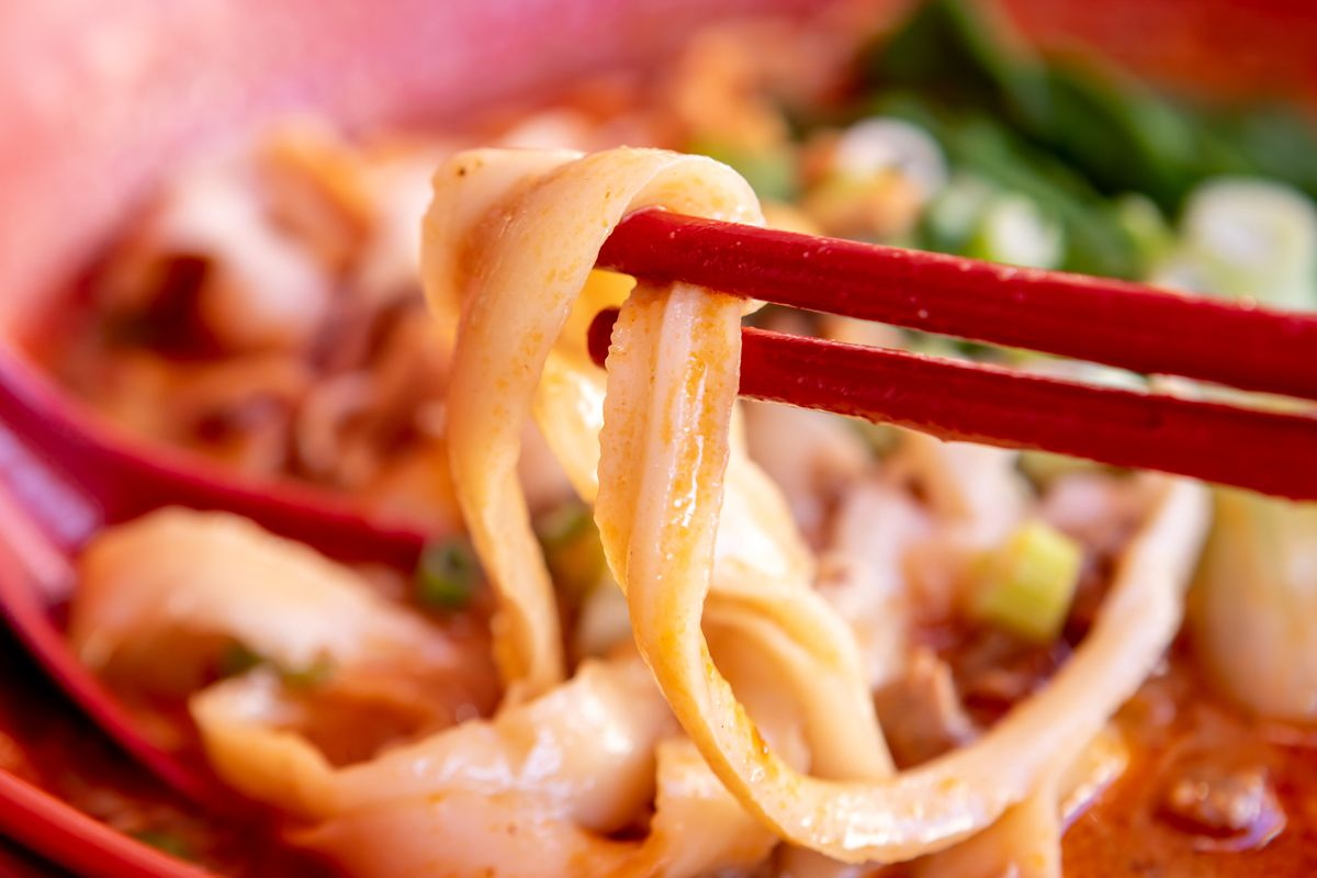 Close-up view of knife-cut noodles being picked up by a pair of chopsticks