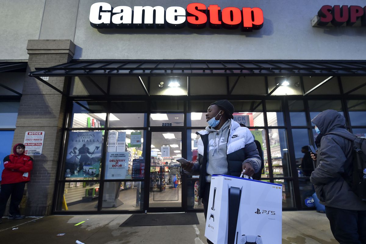 A man wearing a face mask leaves Game Stop with the new...